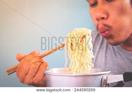 Asian Man Eating Instant Noodles In Pot