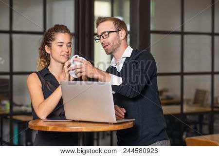 Business Partners Chatting And Working At Cafe Table. Man And Woman Using Laptop Computer, Holding C