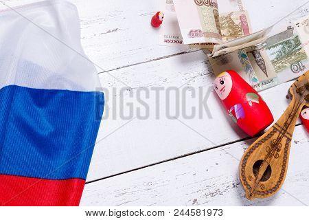 Russian Symbols Matryoshka, Balalaika, Rubles Cash And Flag Of Russian Federation On Wooden Backgrou