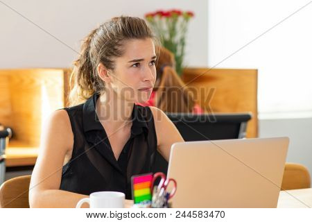 Serious Beautiful Business Woman Working On Laptop Computer. Businesswoman Sitting At Desk With Blur