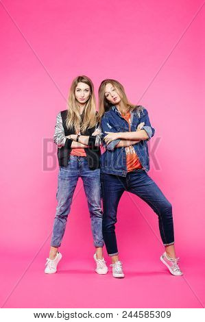 Fashionable Sisters In Jeans, With Long Blonde Hair, Make Up, Posing With Crossed Arms, Confident Lo