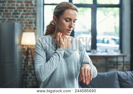 Heart Rate. Appealing Mature Woman Gazing At Smart Watch And Putting Hand On Neck