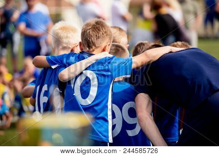 Young football players in blue jersey sportswear. Group photo with football coach. Young sports team with football coach. Pep talk with coach before the final match. Football school tournament for young boys