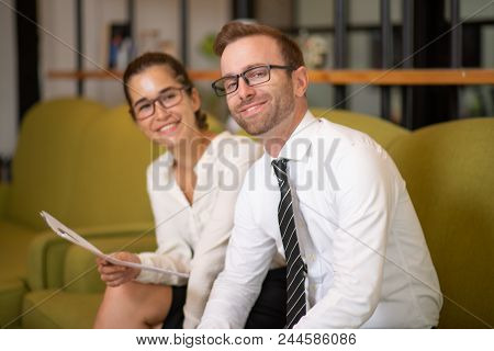 Smiling Coworkers Sitting On Couch In Office Lobby. Business Man And Woman Looking At Camera And Hol