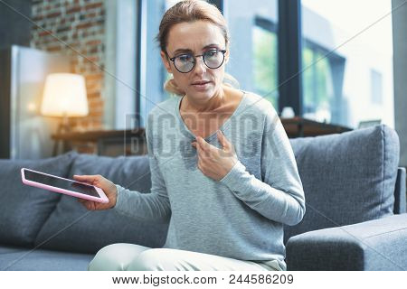Electronic Correspondance. Troubled Mature Woman Using Tablet And Having Hot Flash