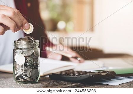 Business Man Saving Money With Putting Coin In Glass And Calculating For Financial Saving, Finance A