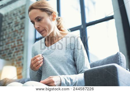 Gradual Process. Beautiful Mature Woman Touching Sweater And Having Hot Flash
