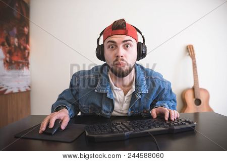 Adult Gamer Looks At The Computer Monitor With Astonished Face. A Surprised Man Plays Video Games At
