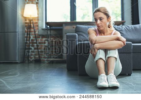 Mood Swing. Depressed Mature Woman Sitting On Floor And Hugging Knees