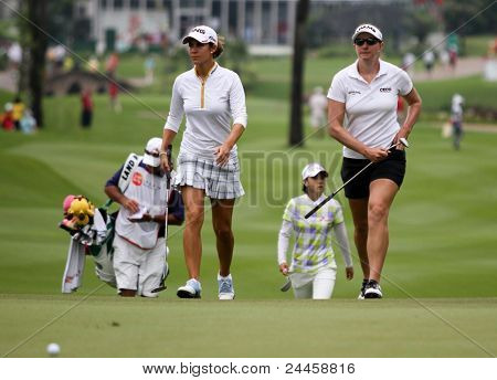 KUALA LUMPUR, MALAYSIA - OCTOBER 16: Azahara Munoz and Brittany Lang approaches the green of the KL Golf & Country Club at the Sime Darby LPGA Malaysia 2011 on Oct 16, 2011 in Kuala Lumpur, Malaysia.