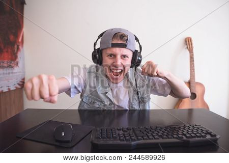 Portrait Of A Joyful Young Gamer Playing Video Games At Home On A Computer. Gamer In Headphones And