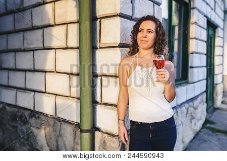 Portrait Of A Beautiful Curly Woman Holding A Glass Of Wine And Leaning A Wall Of House In A Vineyar
