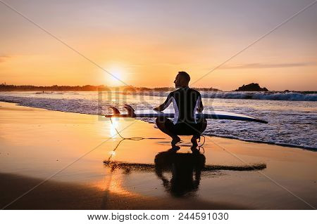 Surfer With Surfboard Sits On Ocean Surf Line At Sunset Time