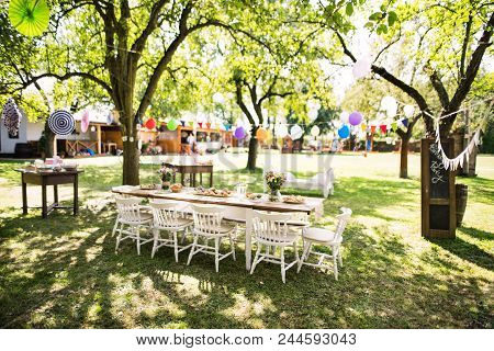 Table Set For A Garden Party Or Celebration Outside. Flowers And Snacks On The Decorated Table In Th
