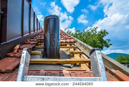 Installing External Chimney Trough A House Roof With Roof Tiles.