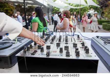 Dj Hand Over Soundboard At Wedding Party. People Dancing Background