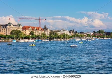 Zurich, Switzerland - May 11, 2018: Lake Zurich, Buildings Of The City Along The Lake, Summits Of Th