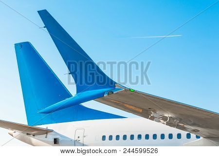 Winglets Wings Of The Aircraft's Tail And Fuselage Against The Blue Sky With The Airplane On The Fli