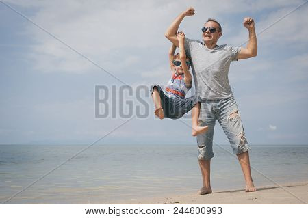 Father And  Son Playing On The Beach At The Summer Day Time. People Having Fun Outdoors. Concept Of