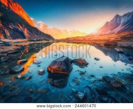 Beautiful Landscape With High Mountains With Illuminated Peaks, Stones In Mountain Lake, Reflection,
