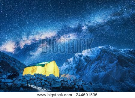 Milky Way, Yellow Glowing Tent And Mountains. Amazing Scene With Himalayan Mountains, Blue Starry Sk