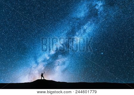 poster of Silhouette of man with trekking poles against amazing Milky Way at night. Space background. Landscape with man on the hill, bright milky way, sky with stars. Beautiful galaxy. Travel. Blue starry sky