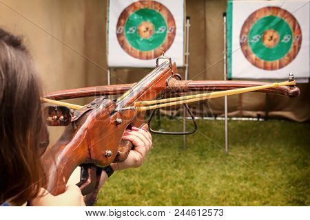 Shooter In The Dash Prepares For A Shot And Aims A Crossbow At The Target. Toned