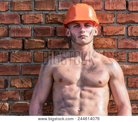 Builder With Muscular Torso And Helmet, Brick Wall On Background. Hard Worker Concept. Athlete With