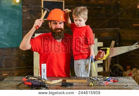 Boy, Child Cheerful Holds Toy Saw, Having Fun While Handcrafting With Dad. Fatherhood Concept. Fathe