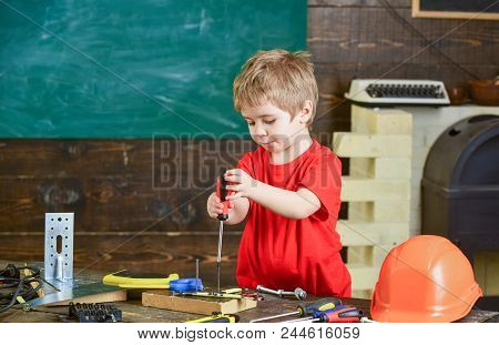 Toddler On Busy Face Plays With Screwdriver Tool At Home In Workshop. Kid Boy Play As Handyman. Chil