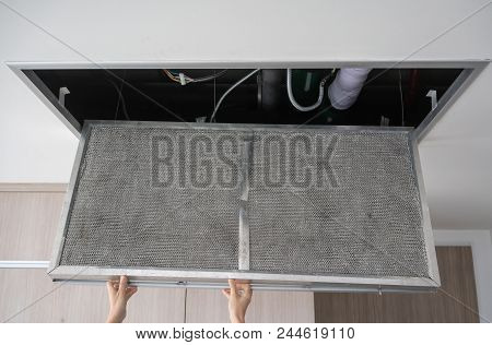 Hand Reaching Up To Open Filter Holder For Air Conditioning Filter In Ceiling