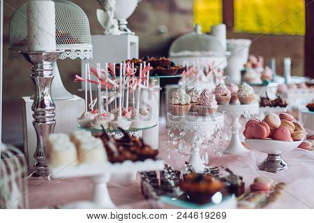 Delicious sweets on candy buffet. Wedding candy bar with a lot of colorful macaroons and another desserts. Wedding party candy bar. poster