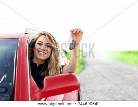 An Attractive Woman In The Red Car Holds A Car Key In Her Hand. Rent Or Purchase Of Auto - Concept.