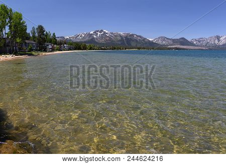 Landscape With Clear Water Of Lake Tahoe, Sandy Beach,homes,trees And Moutains.