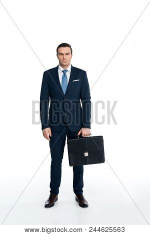 Full Length View Of Serious Middle Aged Businessman Holding Briefcase And Looking At Camera On White