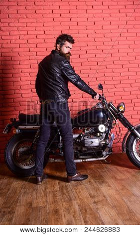 Masculine Hobby Concept. Hipster, Brutal Biker On Serious Face In Leather Jacket Sits Down On Motorc