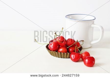 Feminine Still Life Composition. White Enamel Coffee Mug And Sweet Red Cherry Fruit In A Little Meta