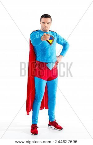 Full Length View Of Confident Male Superhero Standing With Hand On Waist And Pointing At Camera Isol