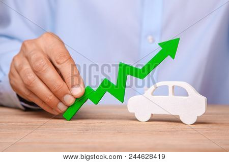 Rising Prices On The Photo. Man Is Holding Green Arrow Up In The Hand And Machine On The Table