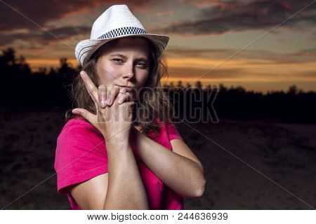 Portrait Of Beautiful American Girl In Cowboy Hat Folded Her Arms With Gun Against  Beautiful Sky At