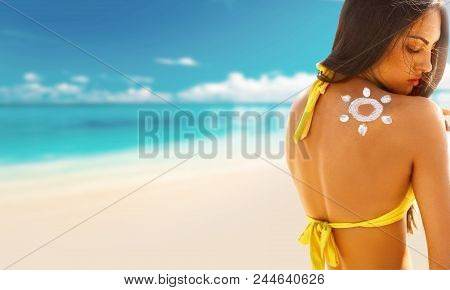 Portrait Of Gorgeous Woman In Bikini With The Drawn Sun On A Shoulder At Beach