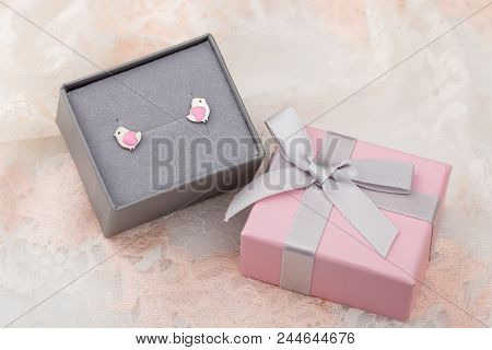 Bird Shape With Hearts Earring Studs In Pink Gift Box On Lace Background. Cute Jewelry For Child Gir