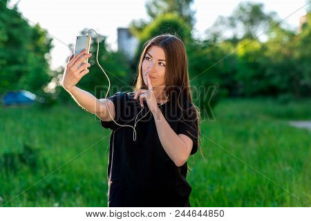 Young Brunette Woman Smiling Happily In Summer In Park. Communicates In Social Networks. Hands Holdi