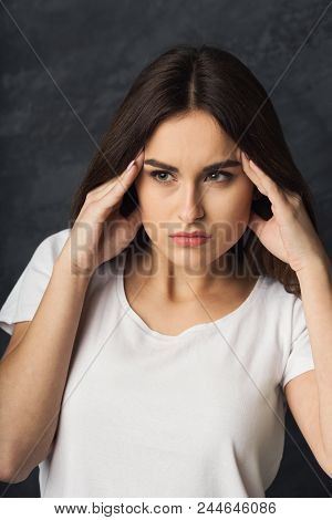 Portrait Of Young Woman Having Headache. Attractive Girl With Migraine At Dark Studio Background. He