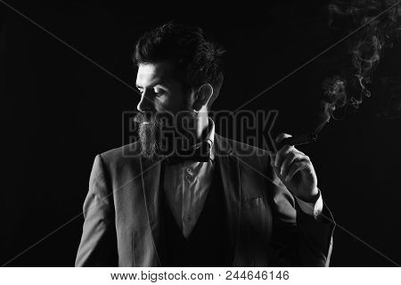 Businessman With Shy Face Expression Smokes Cuban Cigar. Man With Beard Holds Cigar On Black Backgro