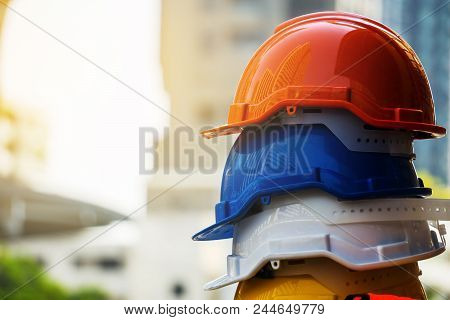 Orange, Blue, White And Yellow Hard Safety Helmet Hat. Engineer, Construction And Safety Concept. Co