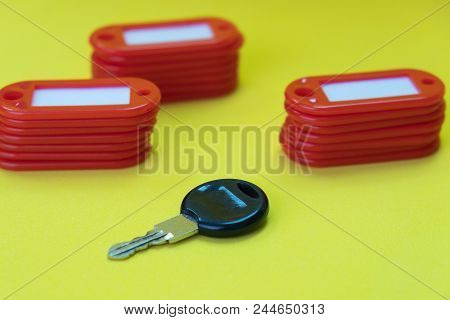Black Key Among Tags For Keys On A Yellow Background, Pile Of Tags And A Key