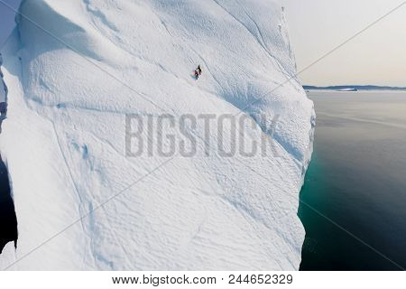 The Climber Climbs The Glacier. Two Climbers On An Iceberg In The Sea.