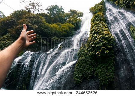 Waterfall In The Rain Forest. The Hand Points To The Waterfall. Waterfall Beauty Of Nature.