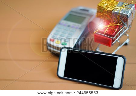 Mobile Payment Concept : Smartphone, Payment Reciever Equipment, And Shopping Cart With Boxes On Woo